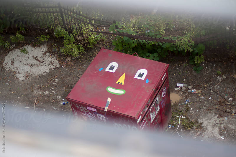 A garbage dumpster decorated with a face by Erik Naumann for Stocksy United