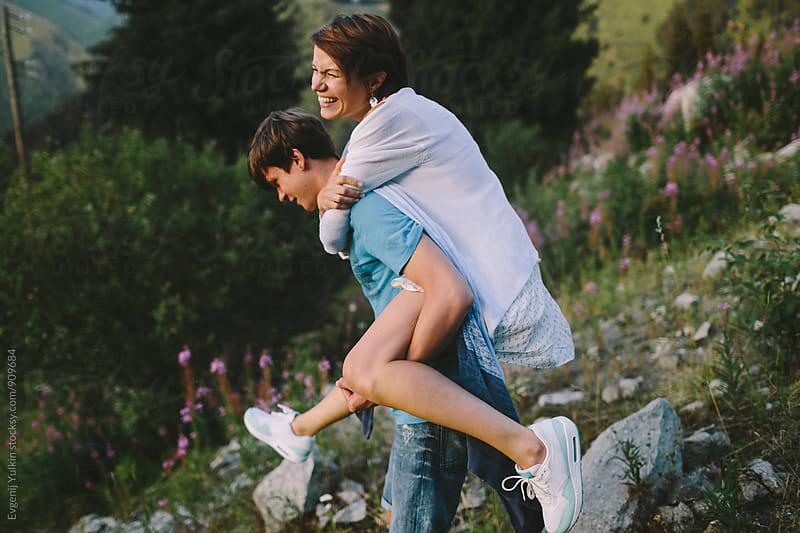 Girl riding on the back of her boy friend by Evgenij Yulkin for Stocksy United