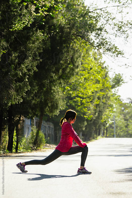 Young woman doing workout before jogging by Maa Hoo for Stocksy United