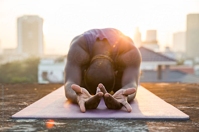 Dark skinned yoga practitioner stretching on a rooftop  by Jovo Jovanovic for Stocksy United