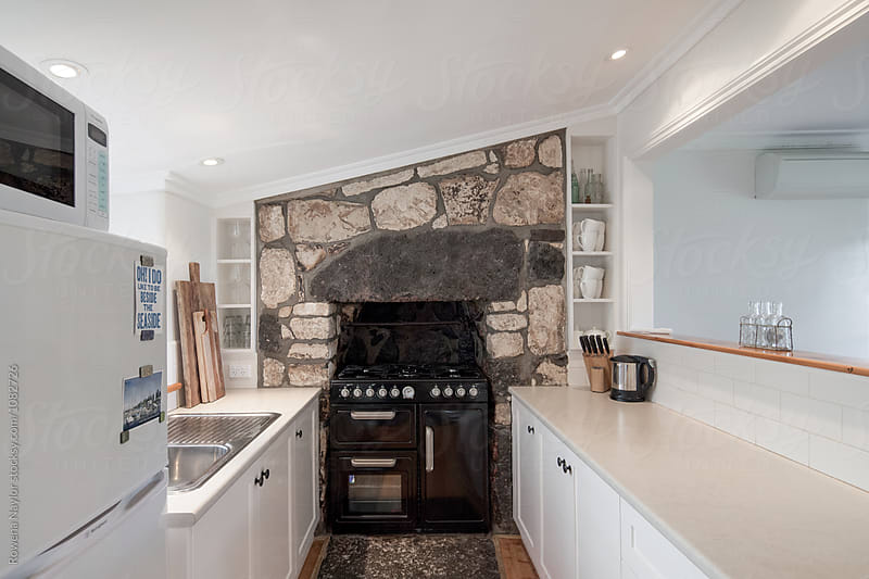 Small country kitchen with Range style cooker by Rowena Naylor for Stocksy United