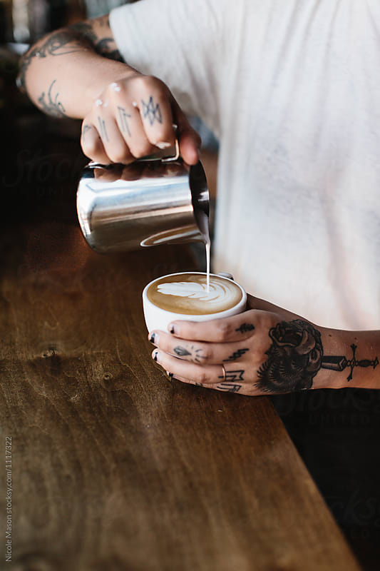 hands with tattoos pouring latte art in white mug