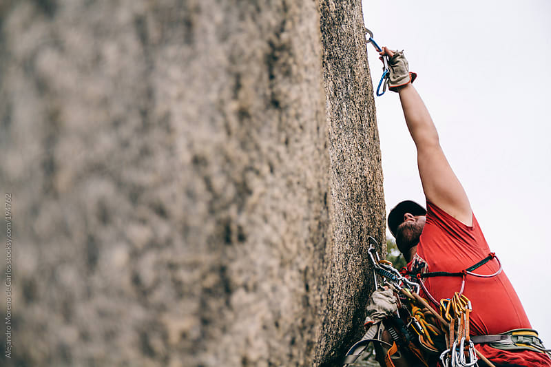 Aid climbing - Man reaching bolt while climbing a route by Alejandro Moreno de Carlos for Stocksy United