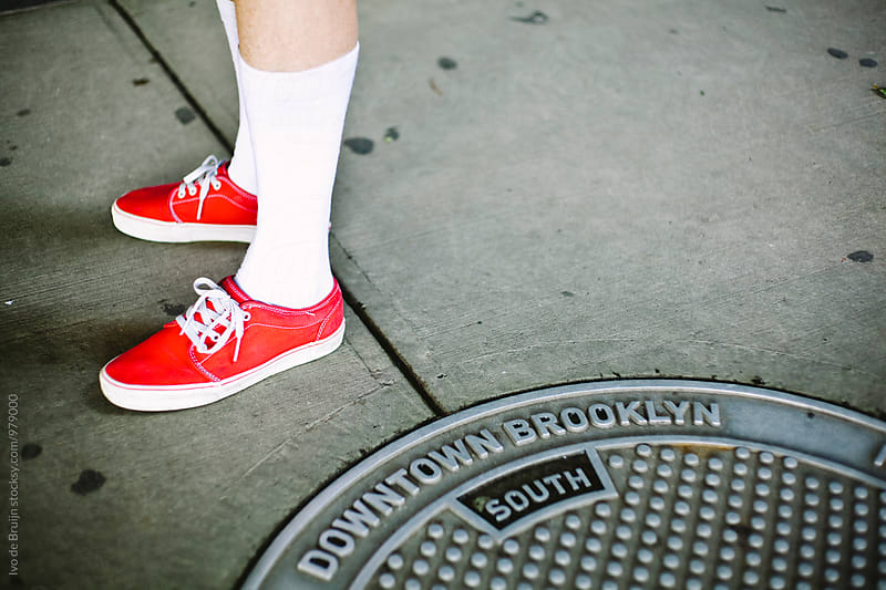 Close up of red someone's red sneakers standing next to a manhole cover in Brooklyn by Ivo de Bruijn for Stocksy United