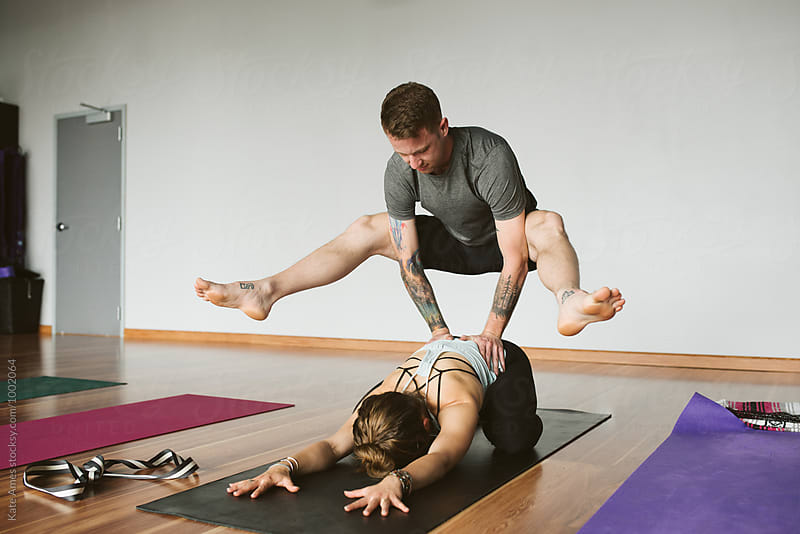 Friends practice partner yoga during studio class. by Kate Daigneault for Stocksy United