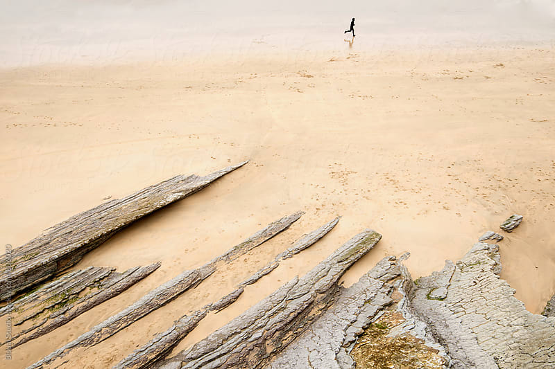 Aerial view of a man running alone in sandy beach by Bisual Studio for Stocksy United