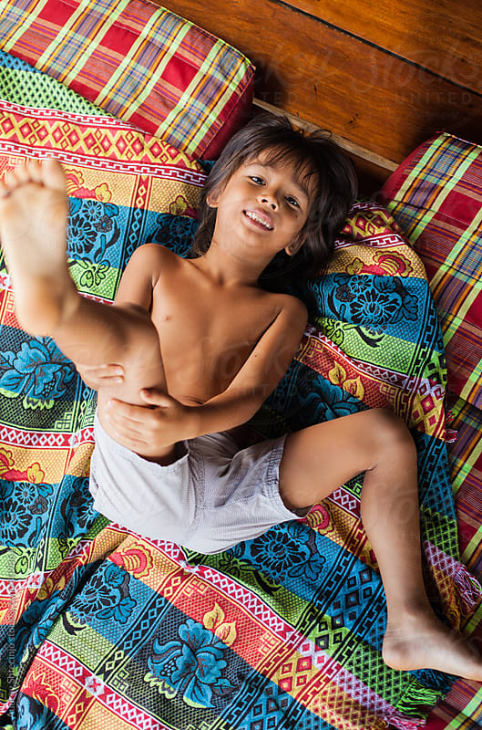Cute little boy playing on colorful mattress. by Audrey Shtecinjo for Stocksy United