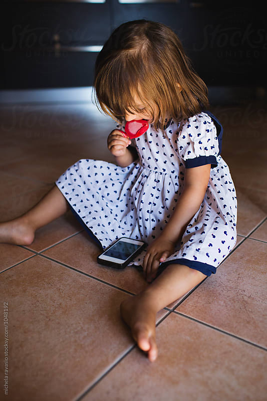 Sitting little girl eating ice cream and watching on the phone by michela ravasio for Stocksy United