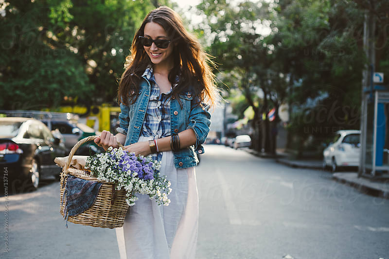 Beautiful girl walking down the streets, holding a basket full of wildflowers. by Jovo Jovanovic for Stocksy United