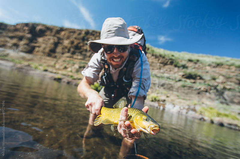 happy fly fisherman with a caught yellow fish by Micky Wiswedel for Stocksy United