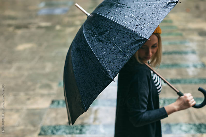 Side view of a woman holding an umbrella in a rainy day. by BONNINSTUDIO for Stocksy United