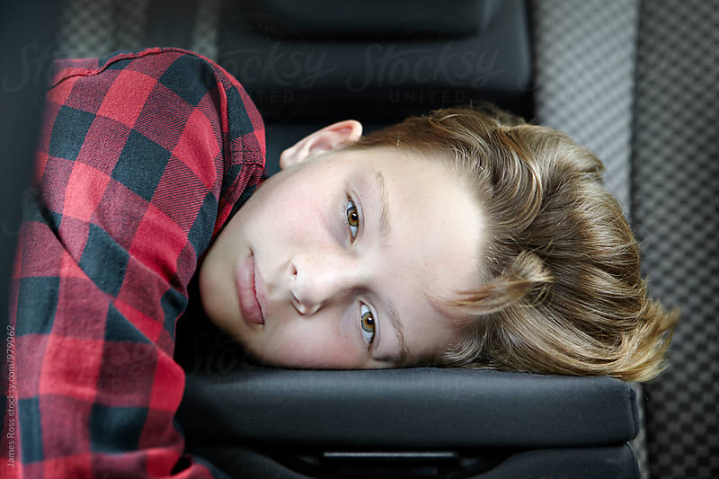 Teenage boy resting his head on car back seat by James Ross for Stocksy United
