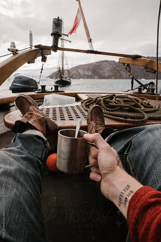 a man in leather boots is lying on a wooden sailing vessel in the hotel after a long journey, tired. Atmosphere of fatigue, depression, rest
