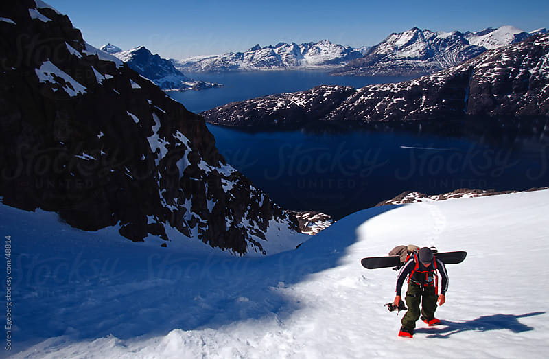 Snowboarder hiking up the mountain above the ocean below by Søren Egeberg Photography for Stocksy United