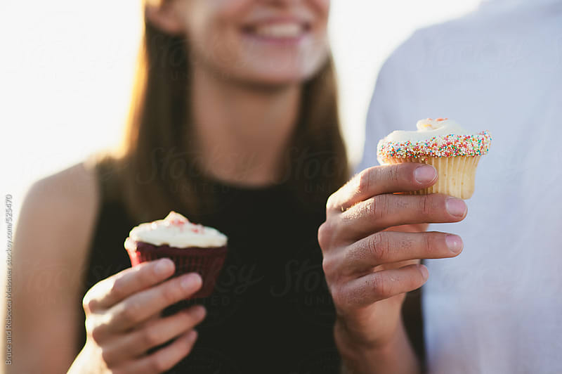Couple enjoying cupcakes by Bruce and Rebecca Meissner for Stocksy United