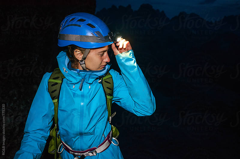 Alpinist woman using the headlamp at night  by RG&B Images for Stocksy United