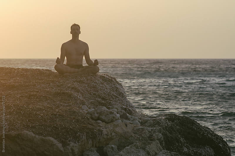 Man Meditating on the Beach, Sunset in the Background by Brkati Krokodil for Stocksy United