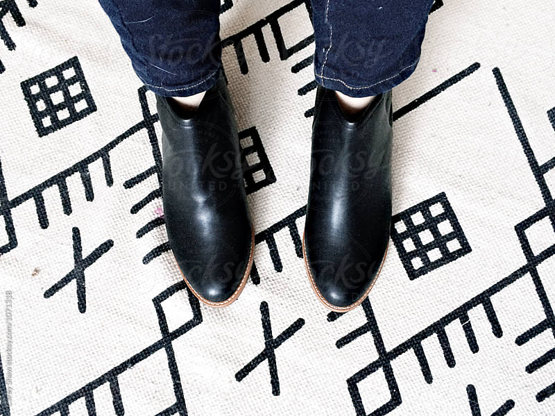 Woman with black leather booties standing on patterned rug by Carey Shaw for Stocksy United