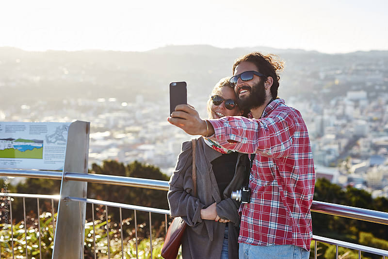 Smiling couple taking selfie against of sunny city by Martí Sans for Stocksy United