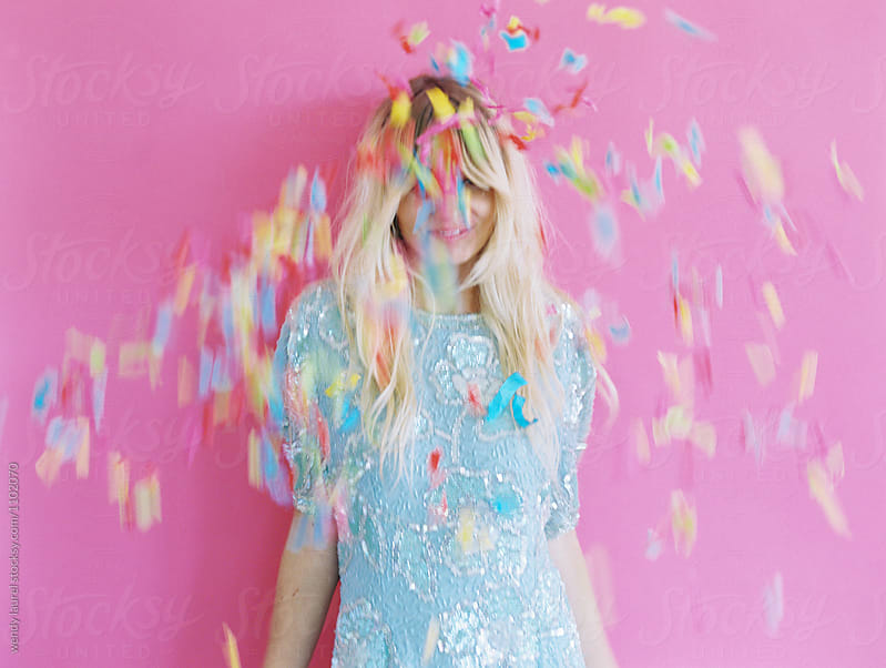 confettit thrown at blonde girl on pink by wendy laurel for Stocksy United
