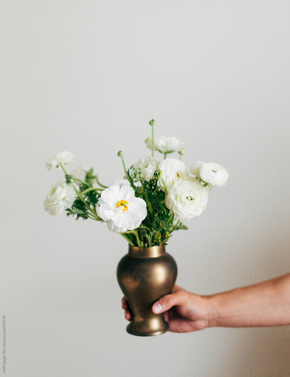 A Person Holds A Brass Vase Of White Flowers Stocksy United
