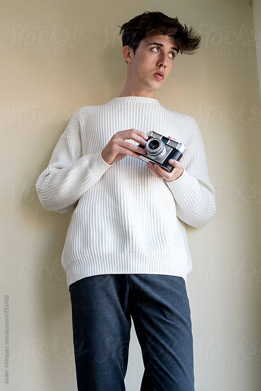 Young Man standing indoors for Spring and Summer Fashion Photo by Javier Marquez for Stocksy United