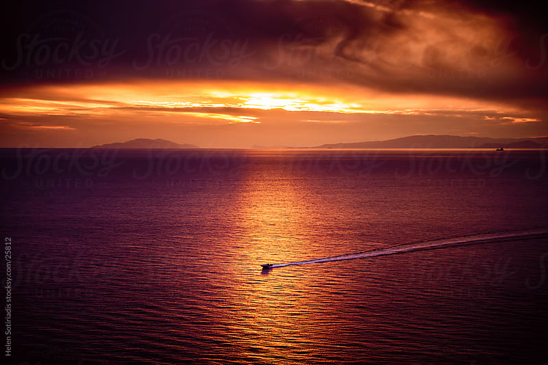 sunset over the sea with a boat by Helen Sotiriadis for Stocksy United