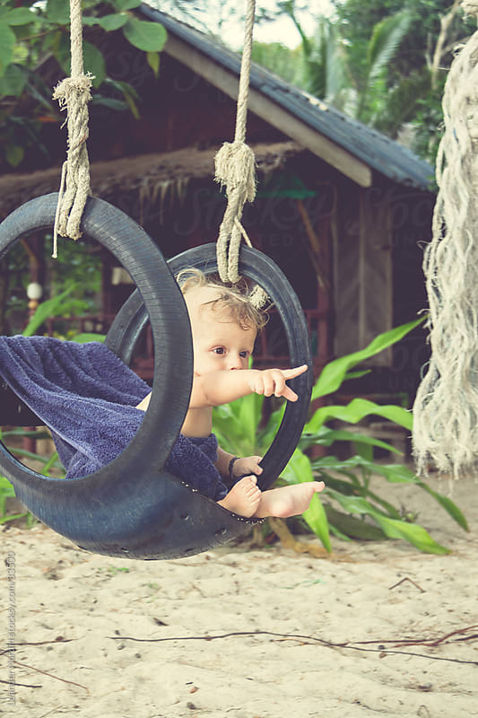 Little boy is relaxing in a swing by Leander Nardin for Stocksy United