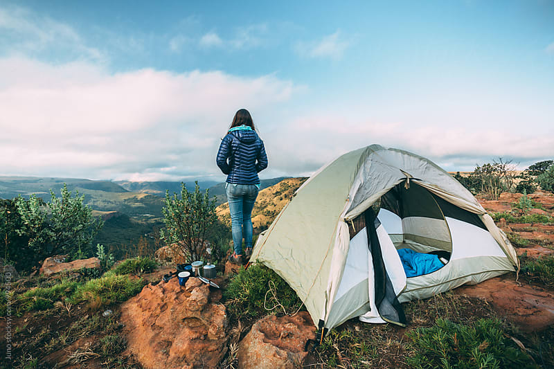 hiker standing outside her camp tent on a mountain summit overlooking a valley view by Micky Wiswedel for Stocksy United
