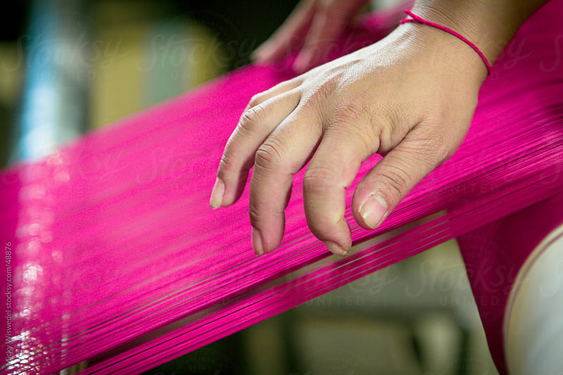 Hand touching silk threads by Micky Wiswedel for Stocksy United
