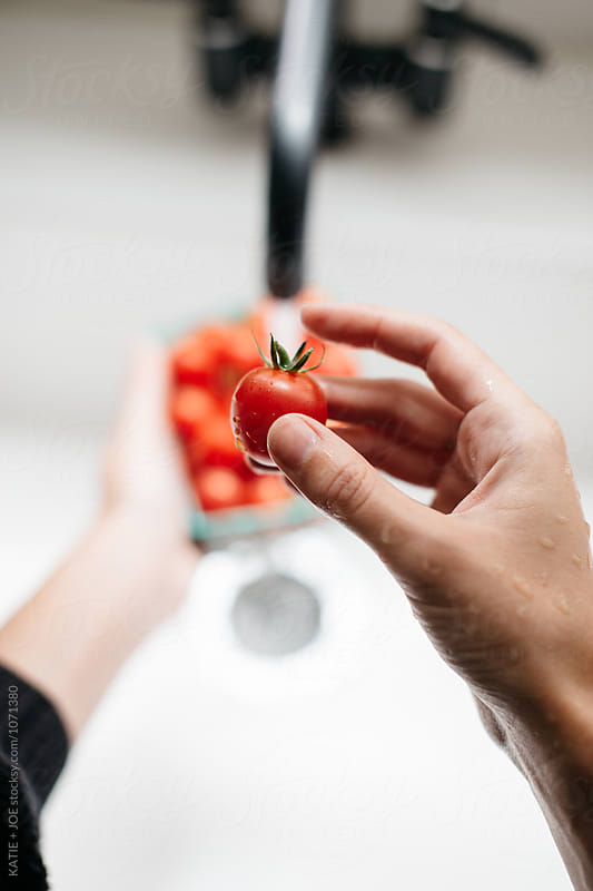 tomatoes being washed in a white sink by KATIE + JOE for Stocksy United