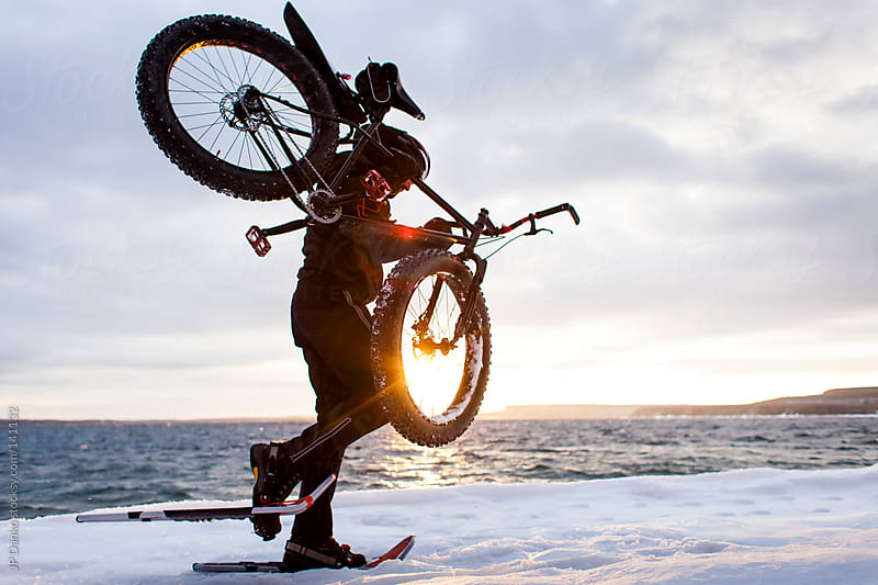 Extreme Winter Sport Man Snowshoeing Carrying Fat Bike by JP Danko for Stocksy United