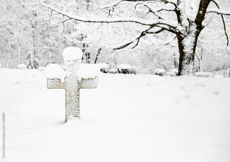Headstone in the shape of a cross is covered in snow by Cara Dolan for Stocksy United
