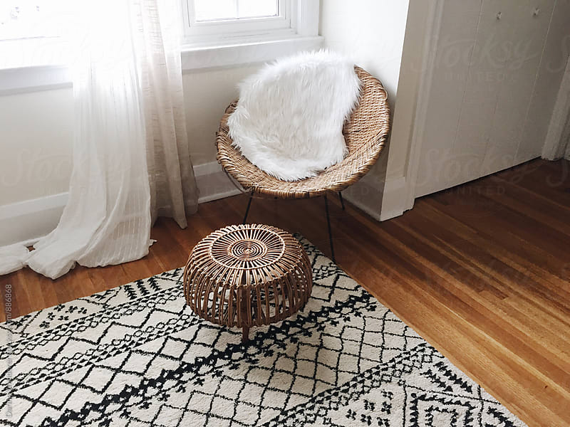 Bohemian living room corner with wicker chair, foot stool and moroccan inspired carpet by Daring Wanderer for Stocksy United
