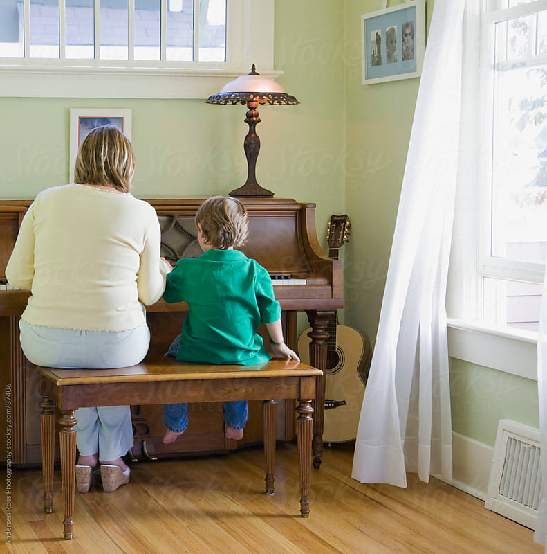 Rear view of woman and boy (4-5) playing piano by Andersen Ross Photography for Stocksy United