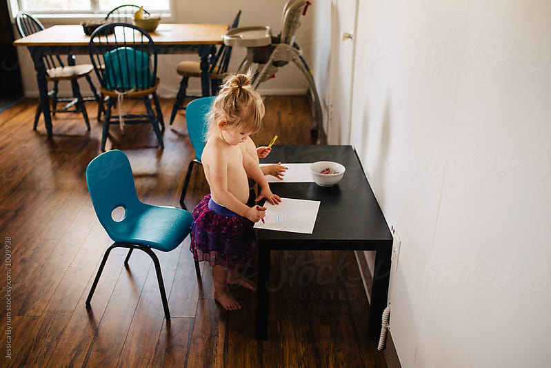Toddler siblings coloring in kitchen. by Jessica Byrum for Stocksy United