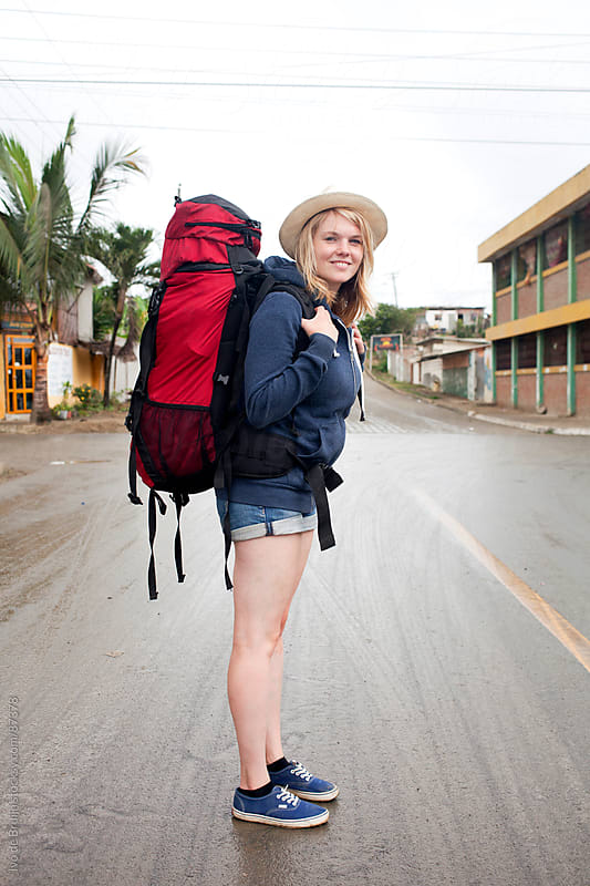 Young smiling happy woman standing with her backpack on holiday by Ivo de Bruijn for Stocksy United