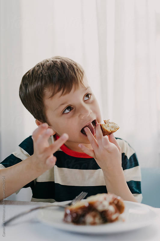 Boy eating treats he helped create  by Cameron Whitman for Stocksy United