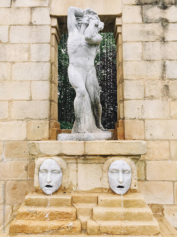 Water fountain with statues of a classical statue of a body and two faces by Luca Pierro for Stocksy United