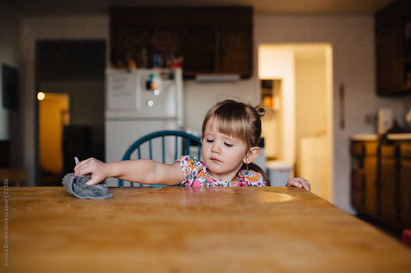 Toddler girl helping wipe the table by Jessica Byrum for Stocksy United