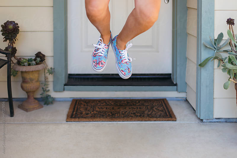Woman's legs jumping on a front porch by Amy Covington for Stocksy United