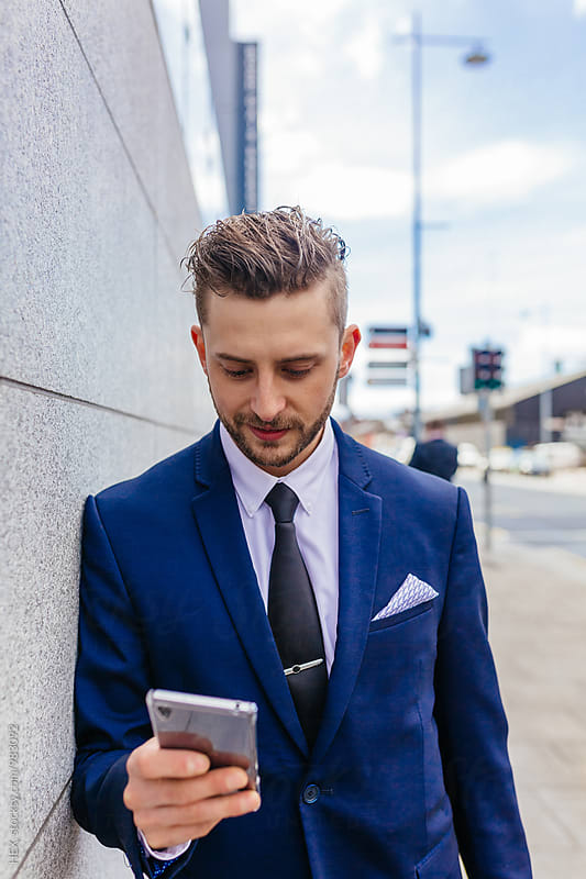 Businessman holding his phone and a briefcase on the street. by Mattia Pelizzari for Stocksy United
