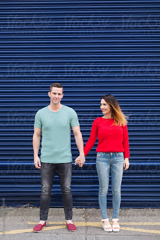 Young Couple Standing Close Against a Blue Shutter by HEX. for Stocksy United