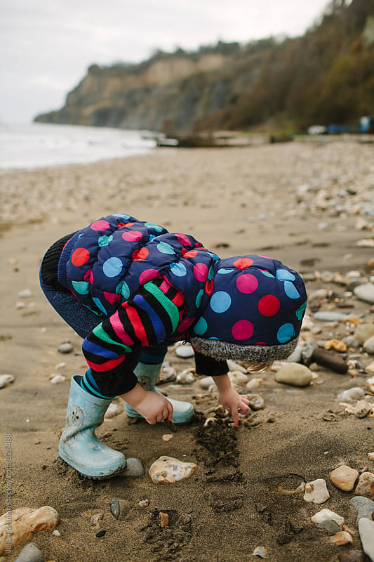 Little girl in brightly coloured clothes drawing in the sand on a beach. by Julia Forsman for Stocksy United