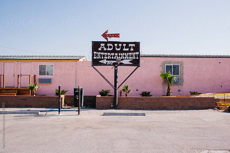 Sign pointing to adult entertainment in front of a pink building by Gary Parker for Stocksy United