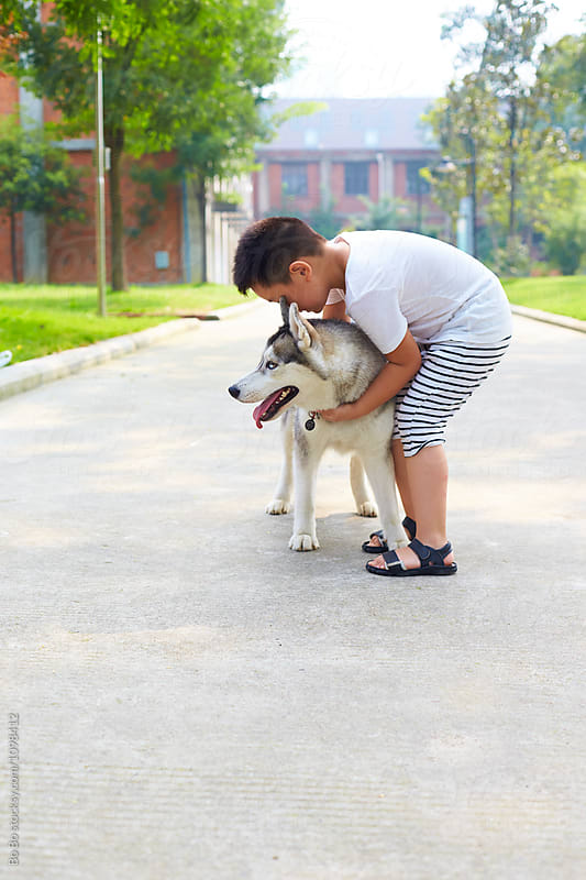 lovely little boy playing with his husky dog outdoor by Bo Bo for Stocksy United