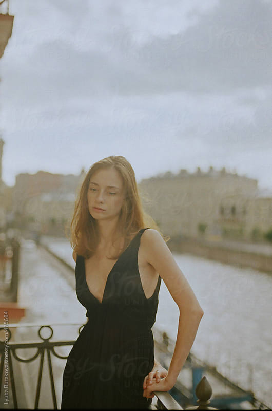 Woman standing on the balcony in historic part of Saint Petersburg by Lyuba Burakova for Stocksy United
