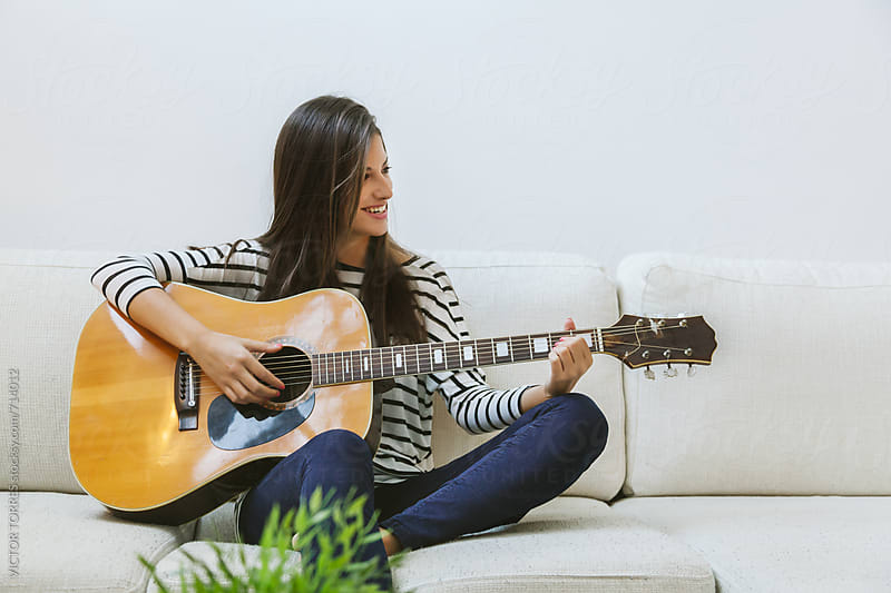 Woman Playing Acoustic Guitar at Home by VICTOR TORRES for Stocksy United