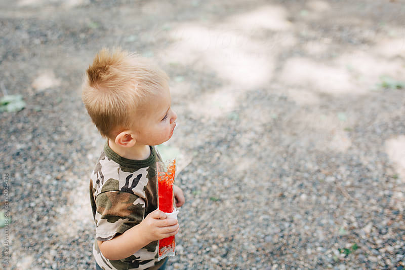 Toddler boy with red popsicle by Jessica Byrum for Stocksy United
