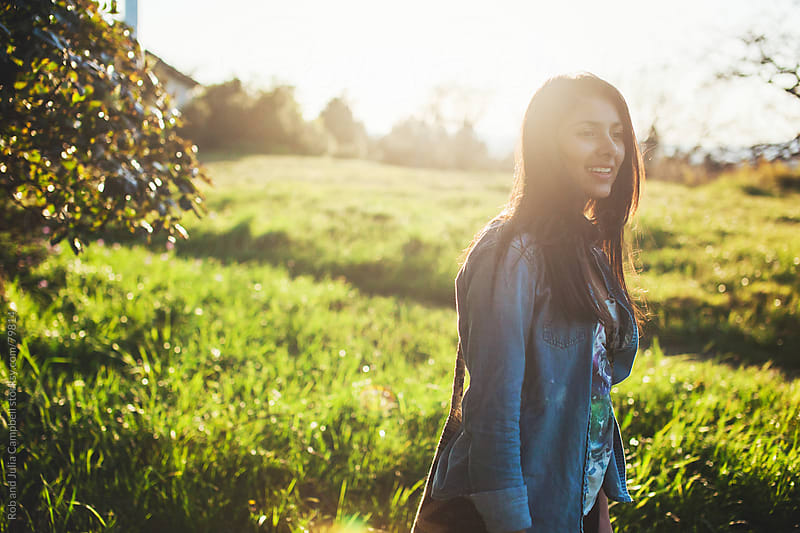 happy, thoughtful teen girl enjoying nature at sunset by Rob and Julia Campbell for Stocksy United
